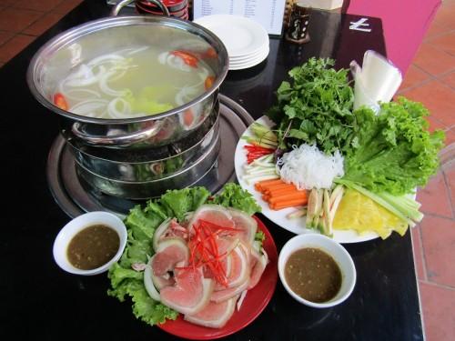 Bò nhúng dấm đầy đủ bao gồm nước dùng, thịt bê tươi, rau sống và một bát mắm nêm trọn vị